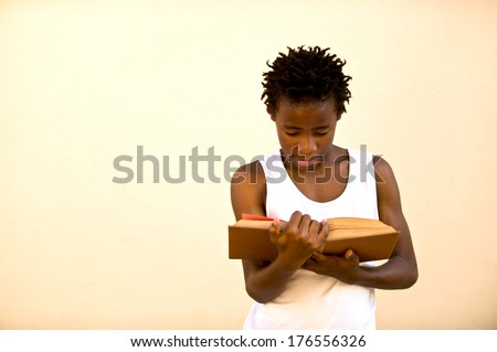 A young African man wearing a white vest reading a book. - stock photo