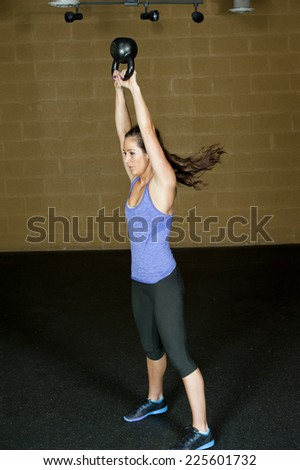 A young and athletic trainer posing with a kettlebell in a gym. - stock photo