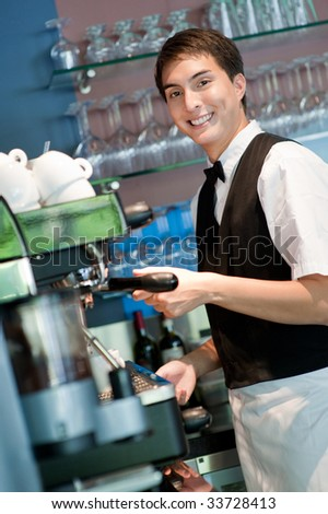 A young and attractive barista making a coffee in an indoor restaurant - stock photo