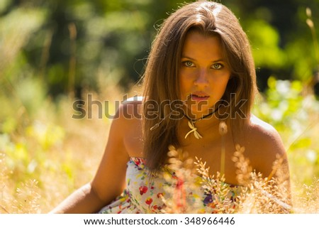 A young and attractive girl in beautiful summer dress middle of sunny meadows. Cheerful girl basking in the warm rays of the summer sun. Beautiful image of a carefree girl. Photos for magazines,  - stock photo