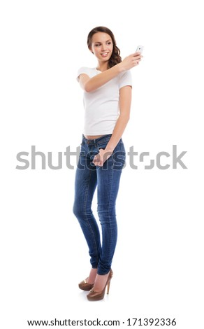 A young and attractive teenage girl with a mobile phone taking picture of herself isolated on white