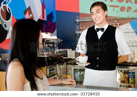 A young and attractive waiter serving coffee to a customer in an indoor restaurant