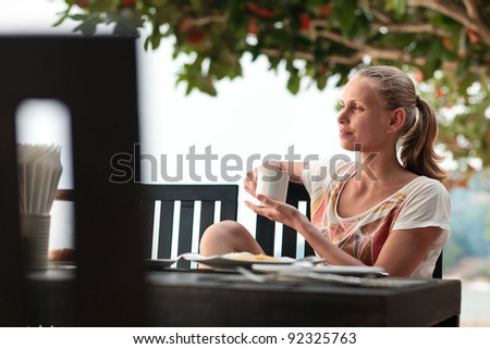 A young and attractive woman having a coffee break in an outdoor restaurant on a beach - stock photo