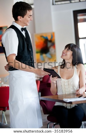 A young and attractive woman paying the bill in a restaurant - stock photo