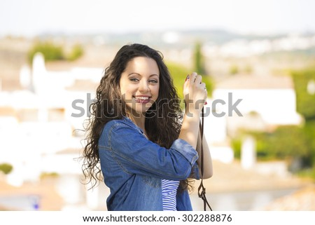 A young and beautiful female tourist taking picture - stock photo