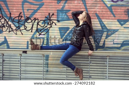 A Young and beautiful girl posing against graffiti wall  - stock photo