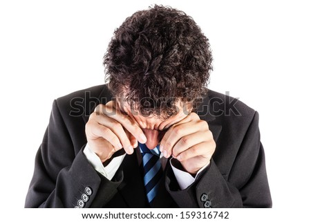 a young and handsome businessman in crying over a white background - stock photo