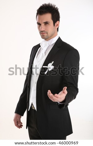 A young and handsome groom in tuxedo lending out a hand towards camera. - stock photo