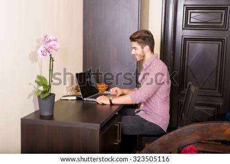A young and handsome man using a laptop computer in a asian styled hotel room.
