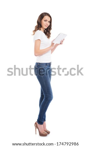A young and happy girl in stylish jeans holding a tablet computer isolated on a white background - stock photo