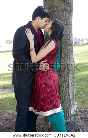 A young and happy Indian couple kissing near a tree in the Fall on a cloudy day. - stock photo