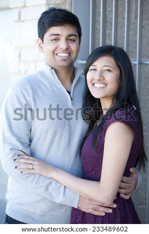 A young and happy Indian couple on a metal steel gray background on a sunny day. - stock photo