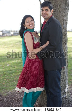 A young and happy Indian couple posing near a tree on a cloudy day in the Fall. - stock photo
