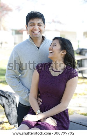 A young and happy Indian couple posing on a picnic table on a sunny day.
