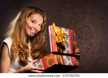 A young and happy teenage girl opening the present - stock photo
