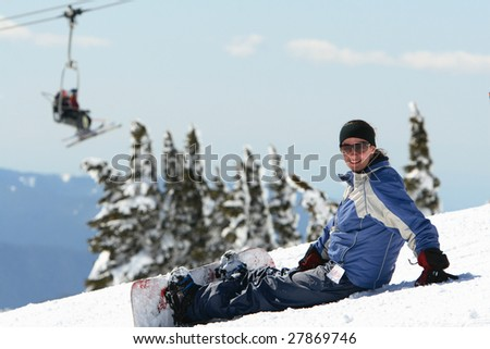 A young and pretty woman enjoying snowboarding on a nice day on the mountain.