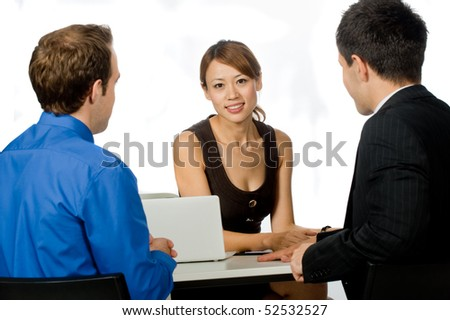 A young and professional businesswoman having a discussion with two of her colleagues on white background