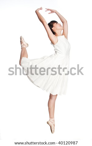 A young asian ballerina does a ballet pose against white background