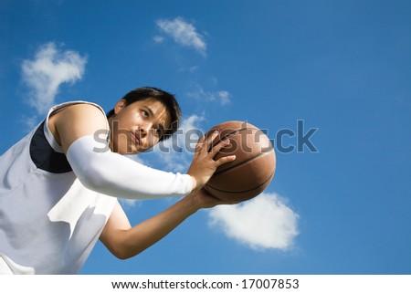 A young asian basketball player shooting a basketball - stock photo