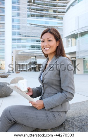 A young asian business woman reading the newspaper at office building - stock photo