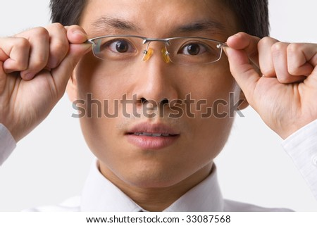 A young Asian businessman gazing at camera while holding glasses to camera
