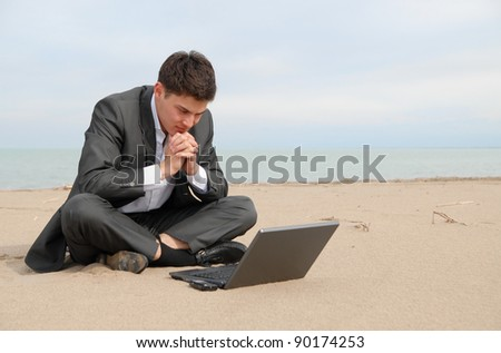 A young Asian businessman sitting on the beach in front of the laptop. He thought about business. - stock photo