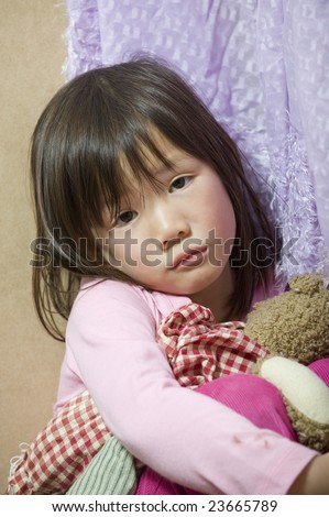 A young asian child holds her hand up as defense from abuse - stock photo
