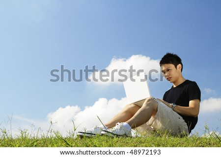 A young Asian college student working with a laptop outdoors - stock photo