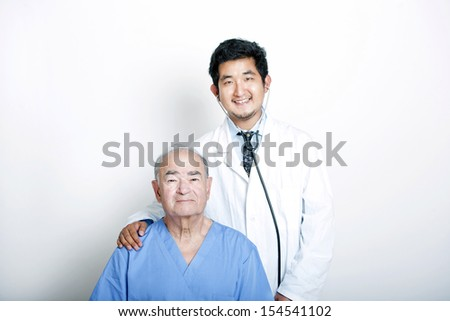 A young Asian Doctor with his hand on the shoulder of a Senior adult patient - stock photo