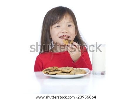 A young asian girl eating a fresh baked cookie. - stock photo