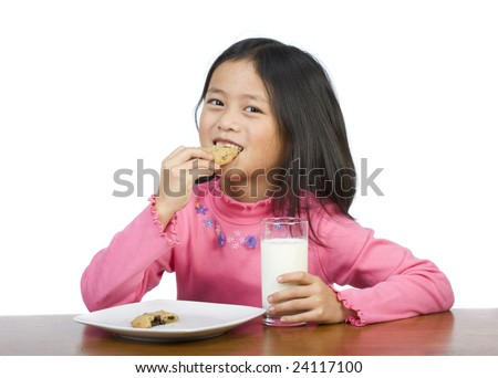 A young asian girl eating a fresh baked cookie.