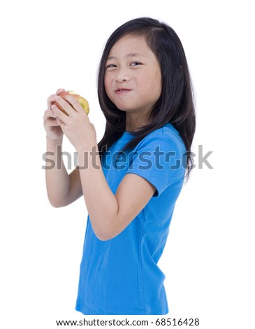 A young asian girl eating a healthy snack. an apple - stock photo