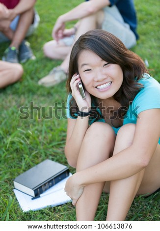 A young Asian girl talking on phone outside with friends in the background - stock photo