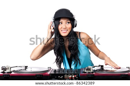 A young Asian girl with a big smile DJing on turntables - stock photo