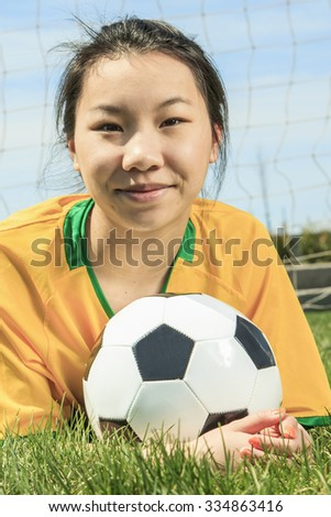 A young Asian girl with soccer ball lay on the ground