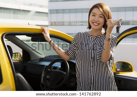 A young Asian lady holding car keys with her yellow car.