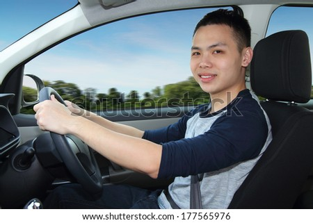 A young Asian man driving - stock photo