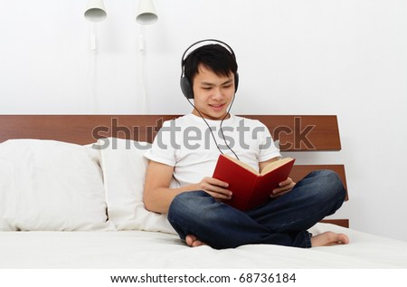 A young Asian man reading a book on a bed - stock photo