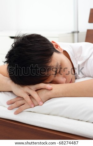 A young Asian man sleeping face down - stock photo