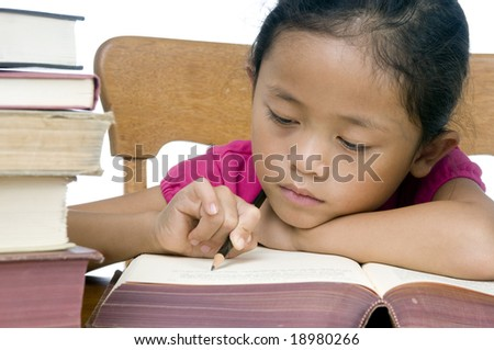 A young asian school girl reading a book. - stock photo