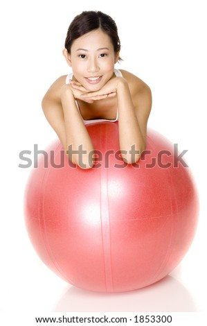 A young asian woman leaning on a sports ball