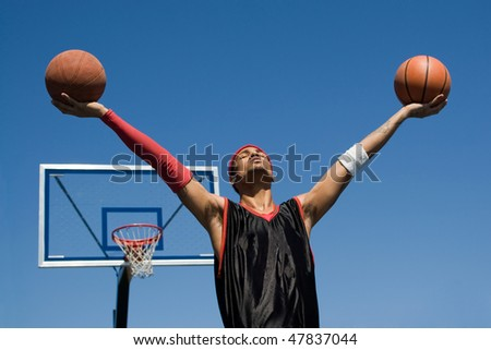 A young athletic build basketball player holding up two basketballs in the air. - stock photo