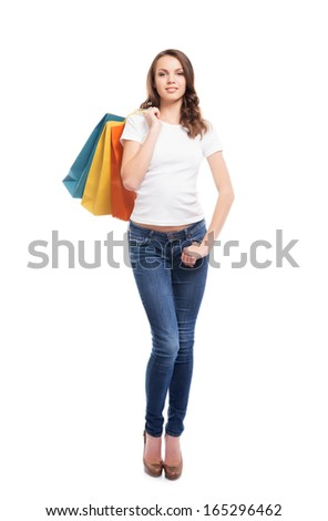 A young, attractive and happy shopping girl with bright shopping bags isolated on white - stock photo