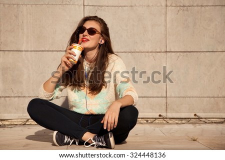 A young attractive brunette girl with long natural hair and stylish clothes posing and drinking juice on urban background. Sunglasses, sweater, jeans. - stock photo