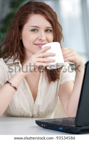 A young attractive business woman sitting in a cafe with a laptop and coffee - stock photo