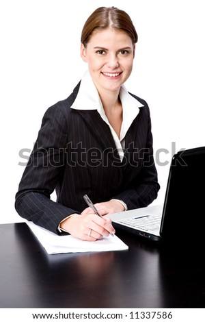 A young attractive businesswoman at a desk with laptop and pen and paper