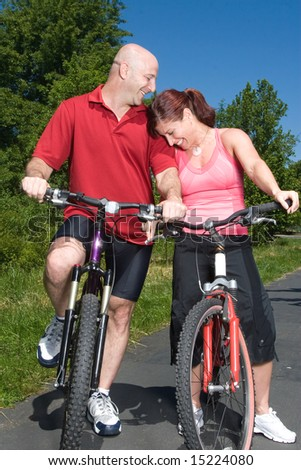 A young, attractive couple at a park, smiles and laughs to each other, while on bicycles. - vertically framed