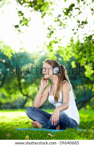 A young attractive girl listening to music in the park - stock photo
