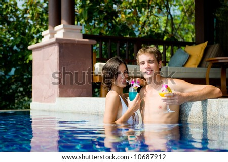 A young attractive in pool with tropical cocktails