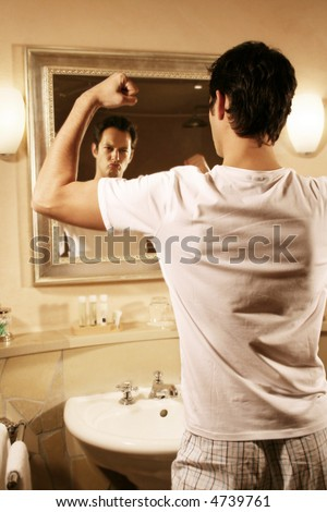 a young attractive man is standing in his bath and flex one ´s muscles - stock photo